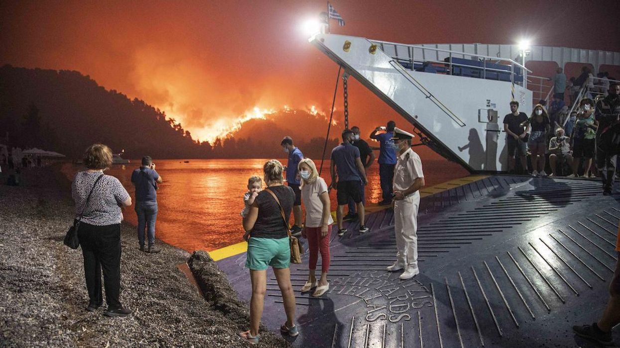 People on a ferry evacuating from a wildfire in Greece.