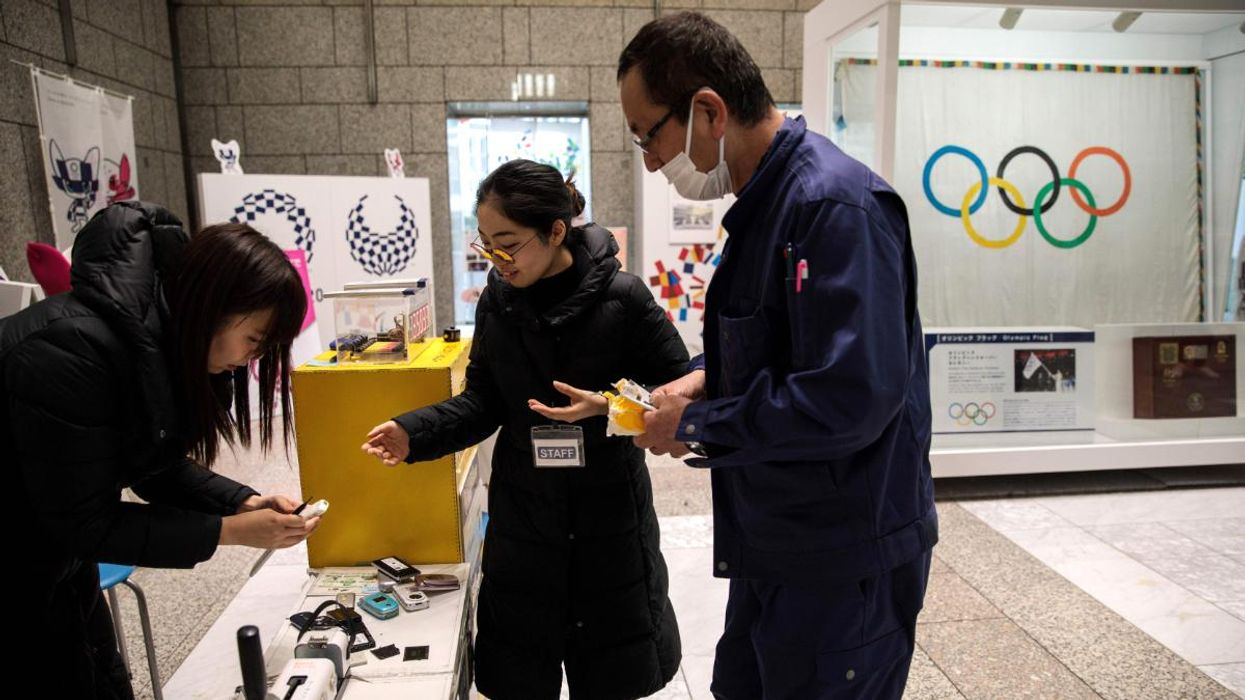 A man hands over used mobile phones in Tokyo.