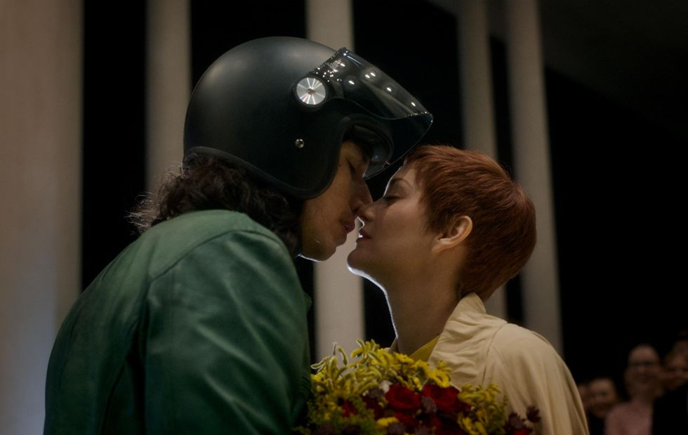 """A movie still from """"Annette."""" It's a tight framed movie still of the actors' side profiles as they lean in for a kiss. Adam Driver (left) wears a green leather jacket and motorcycle helmet. Marion Cotillard (right) wears a bright yellow dress with yellow flowers in hand."""