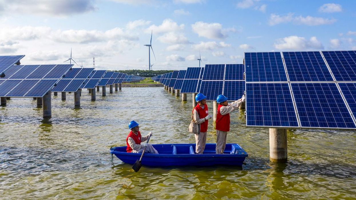 Electrical workers check solar panels in a fishpond in China.