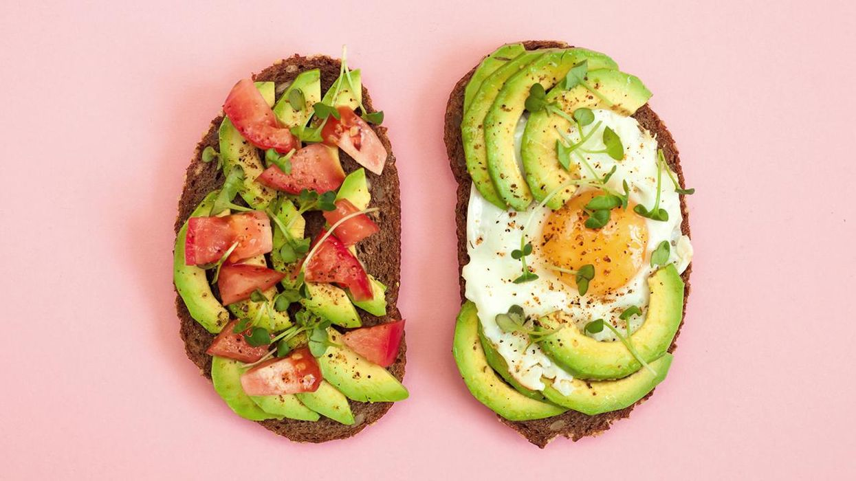 Toasts of dark bread with avocado slices, red tomatoes, fried egg and microgreen
