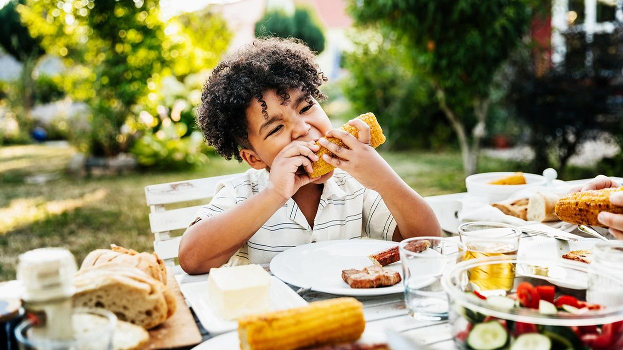 young Boy Eating Barbecued Corn On The Cob