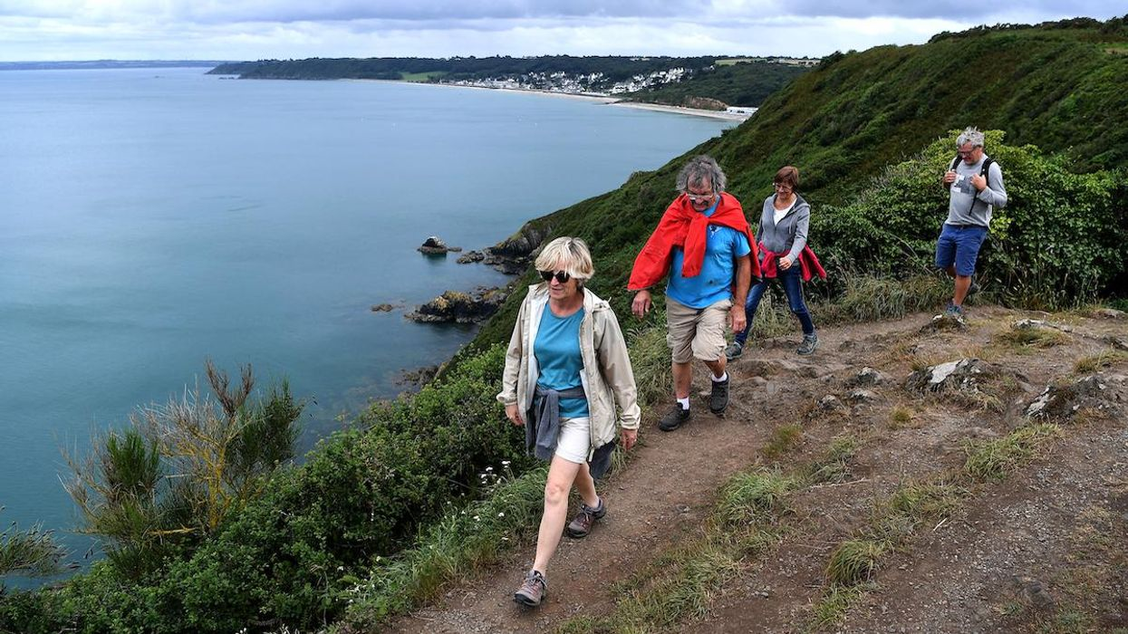 Hikers walk along the coast in France.