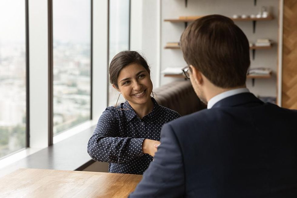 Woman shakes hands with her boss after her performance review