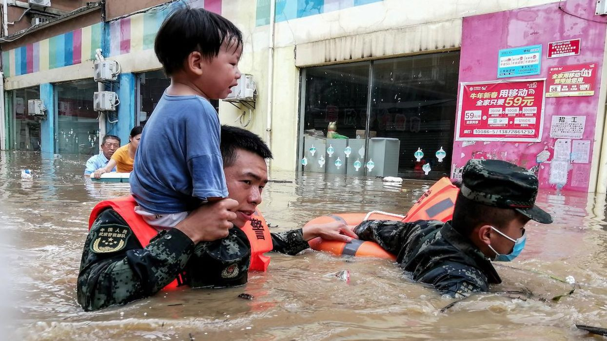 Rescuers evacuate a child from a flood in China.