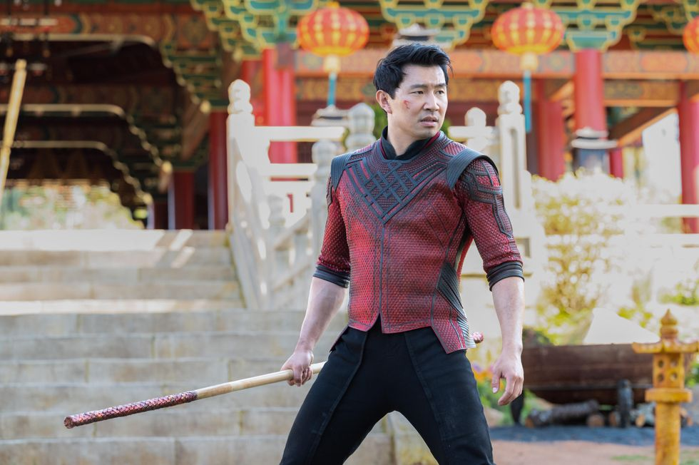 Simu Liu (as Shang-Chi) stands in front of a temple with red pillars. He's holding a bowstaff, and he's wearing red armor made from dragon scales.