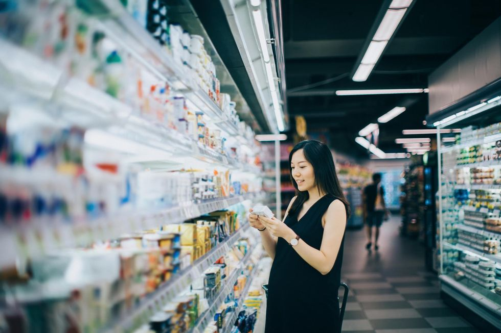 woman grocery shopping in supermarket and reading nutrition label on a packet of cheese