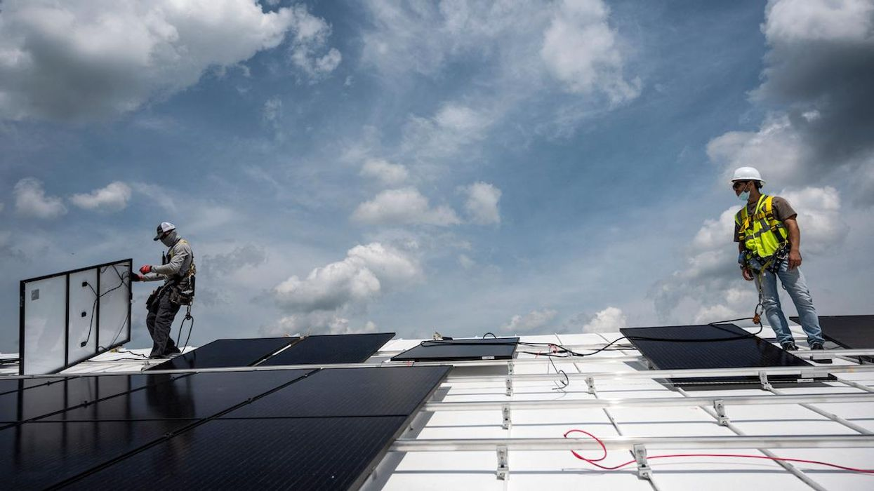 Workers install solar panels on the roof of the Peace Lutheran Church in Virginia.