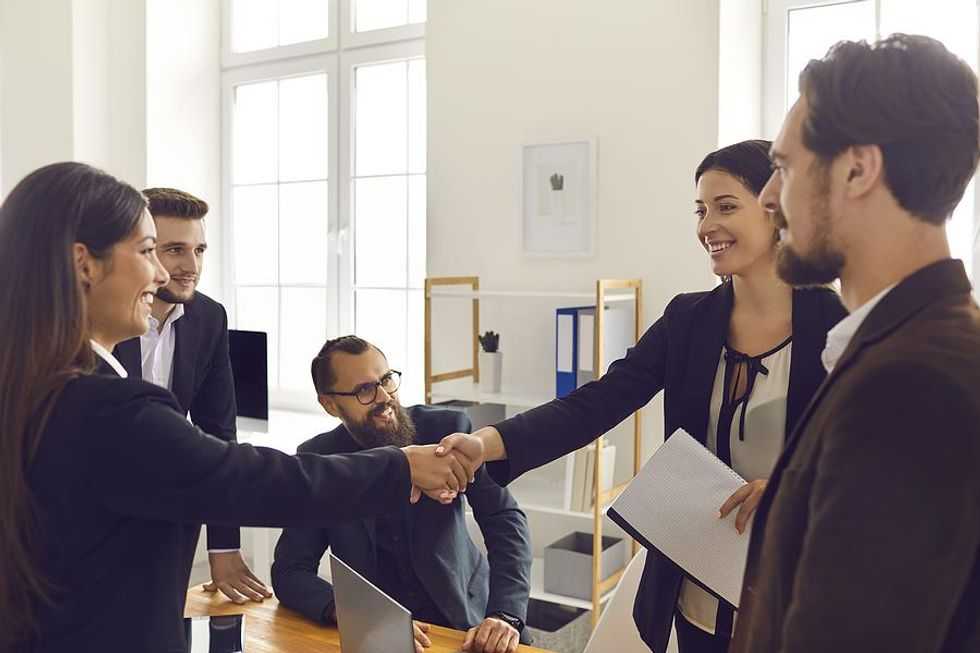 Woman shakes hands with coworkers at her new job