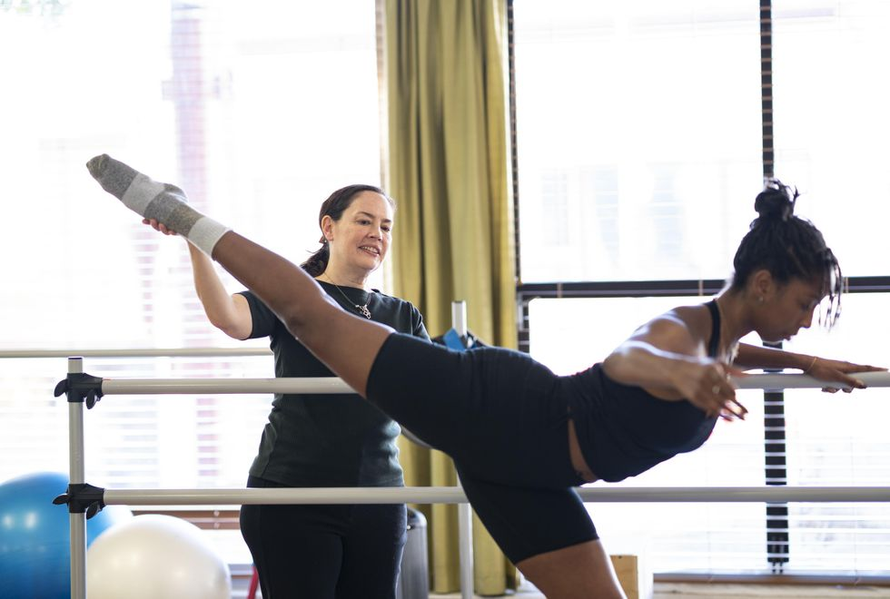 Kendall Alway assists a student in arabesque at the barre. She wears all black and smiles as she lifts the student's ankle.
