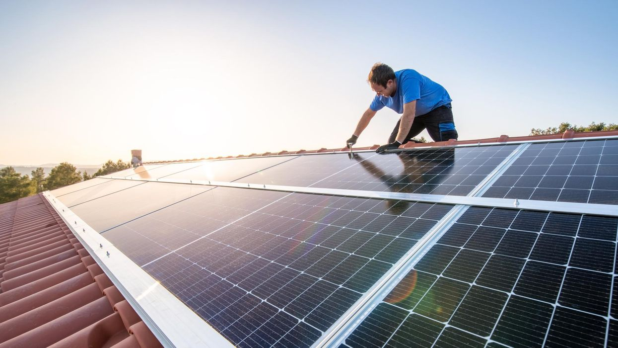 Professional worker installing solar panels on the roof of a house