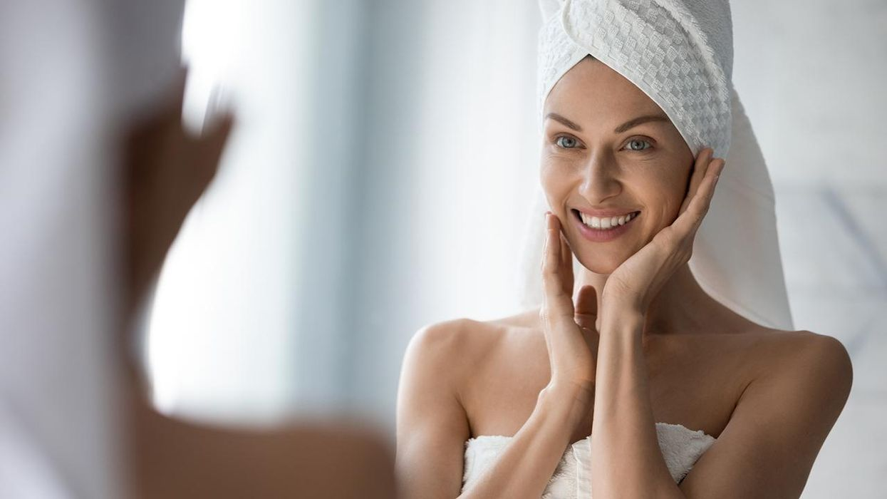 Woman looks in mirror touches moisturized healthy skin feels satisfied