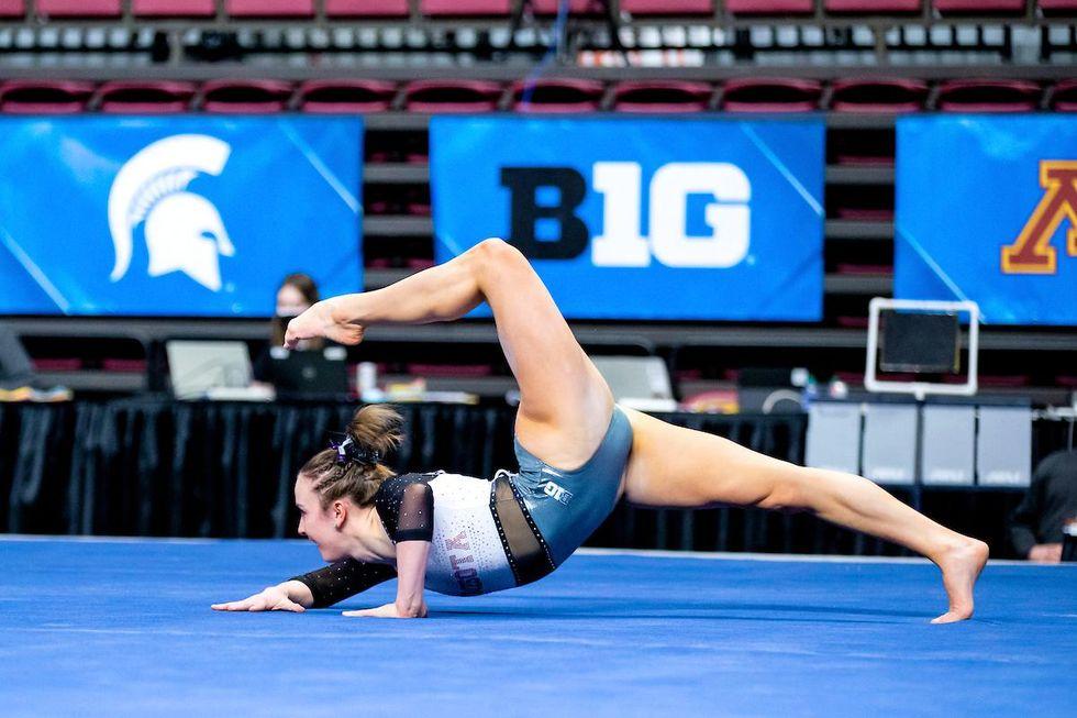 Lexy Ramler crouches on the floor on just her elbows and one foot, with the other curling up over the back of her head
