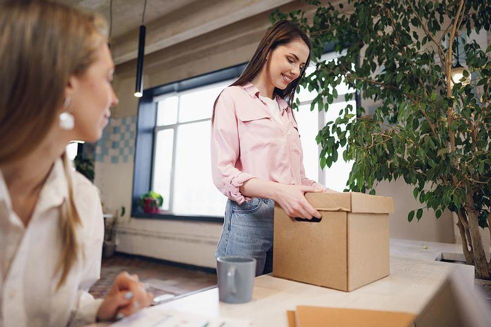 Woman packs up her desk before leaving her job