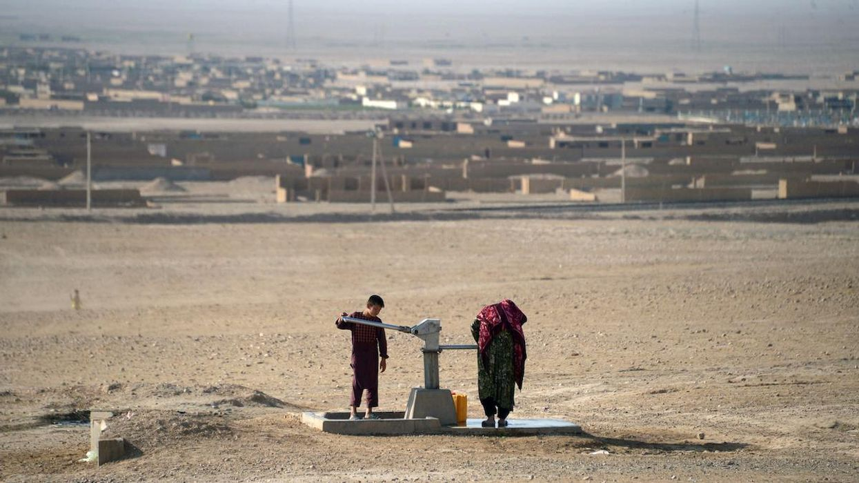 An Afghan boy uses a water pump to collect water during a drought.