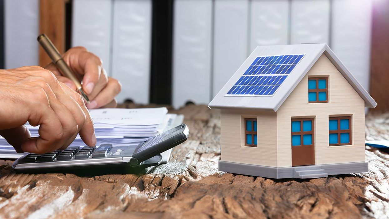 Businessman Using Calculator By Model Home With Solar Panel On Wooden Table