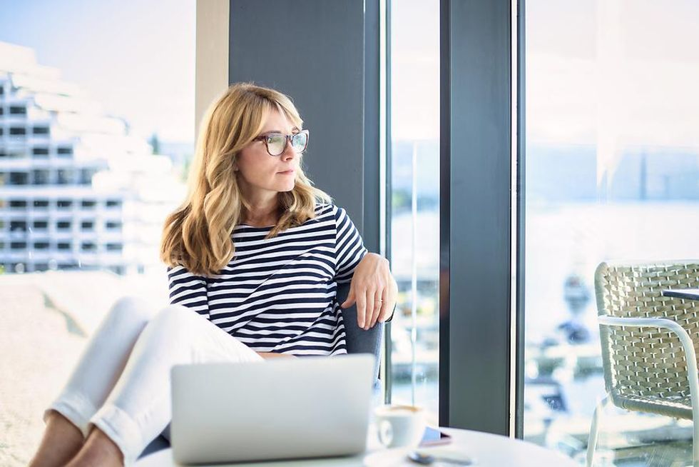 Woman looks out the window at her desk job