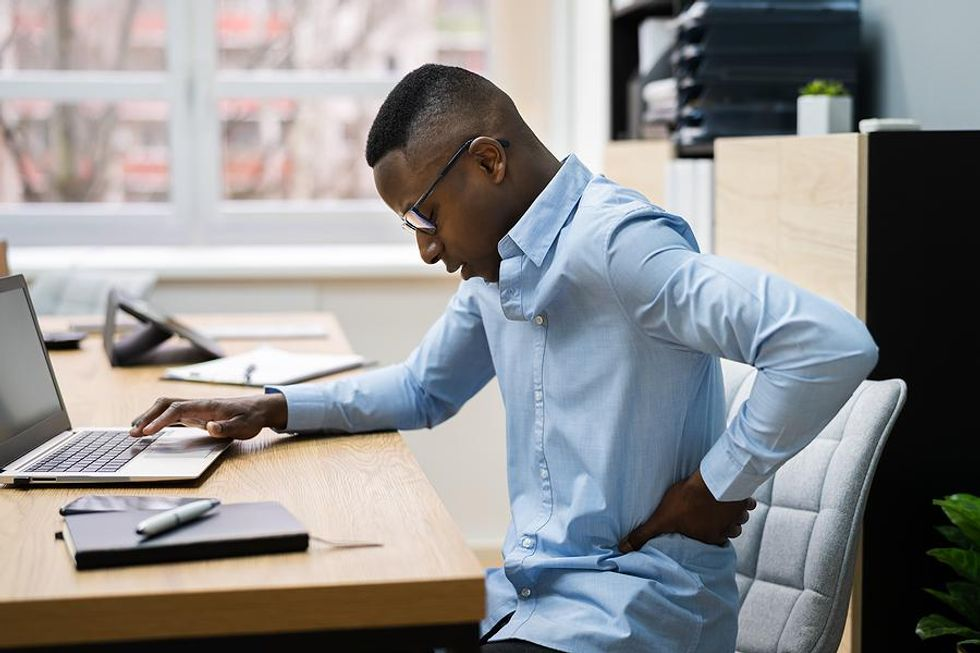 Man experiences back pain at his desk job