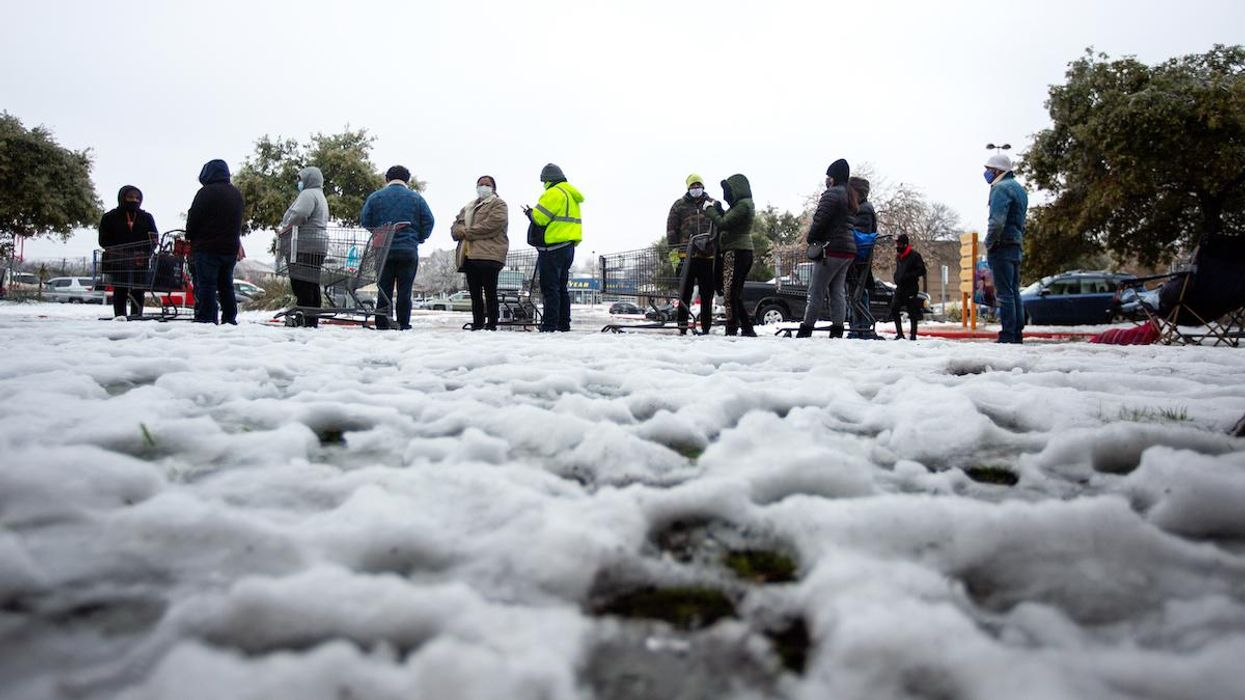 People wait in long lines at a grocery store in Texas following a snowy winter storm.