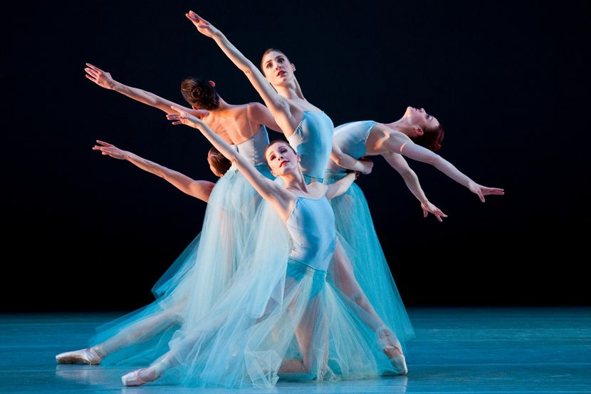 Emily Adams and four other women in light blue leotards and matching long tulle skirts link together, each extending one arm on the diagonal on different levels