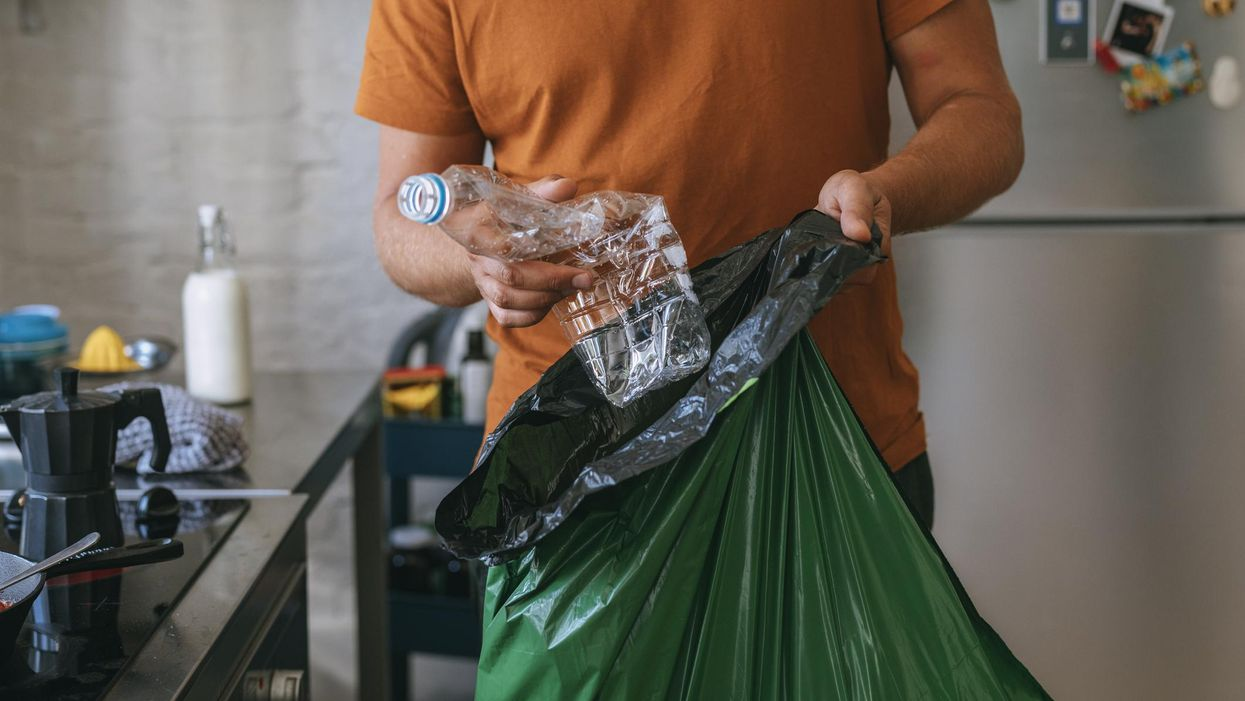 man puts plastic water bottle into green trash recycling bag
