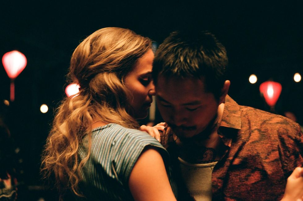 """Kathy (Alicia Vikander) and Antonio (Justin Chon) dance during a dinner party scene in the film """"Blue Bayou."""" Kathy is wearing a green-white striped dress while Antonio wears an open red shirt with a white tank underneath. The photo is a tight, intimate shot of the couple dancing in each other's arms."""