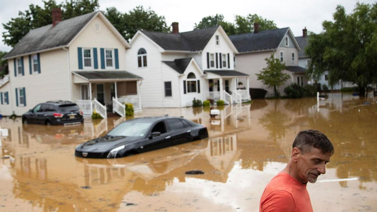 An evacuated resident wades through high water following a flood.