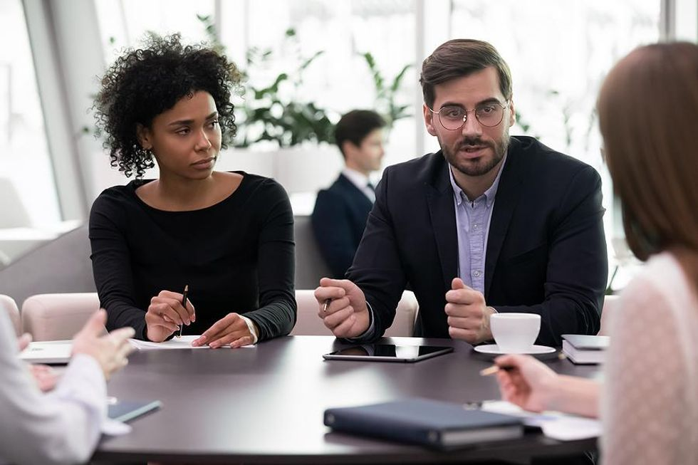 Women listens to her bad boss during a meeting
