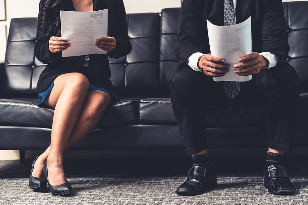Job candidates hold their resumes before an interview