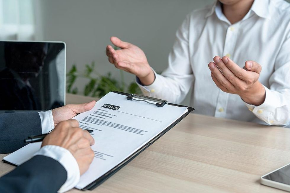 Hiring manager reads a job candidate's resume during an interview