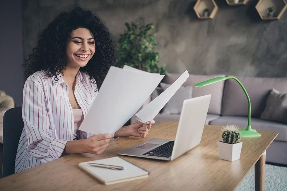 Woman smiles as she reads her resume and cover letter