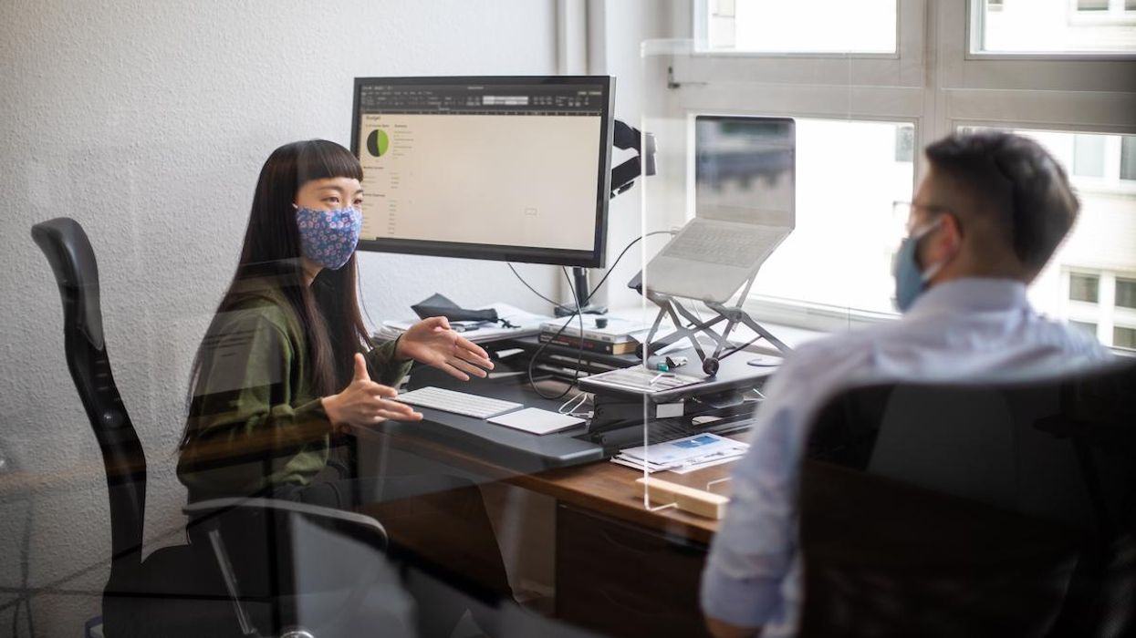 Two office workers wearing cotton face masks.