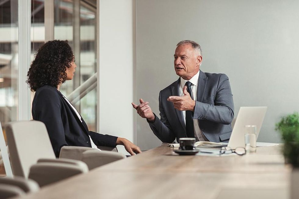 Woman listens to her boss during a performance review