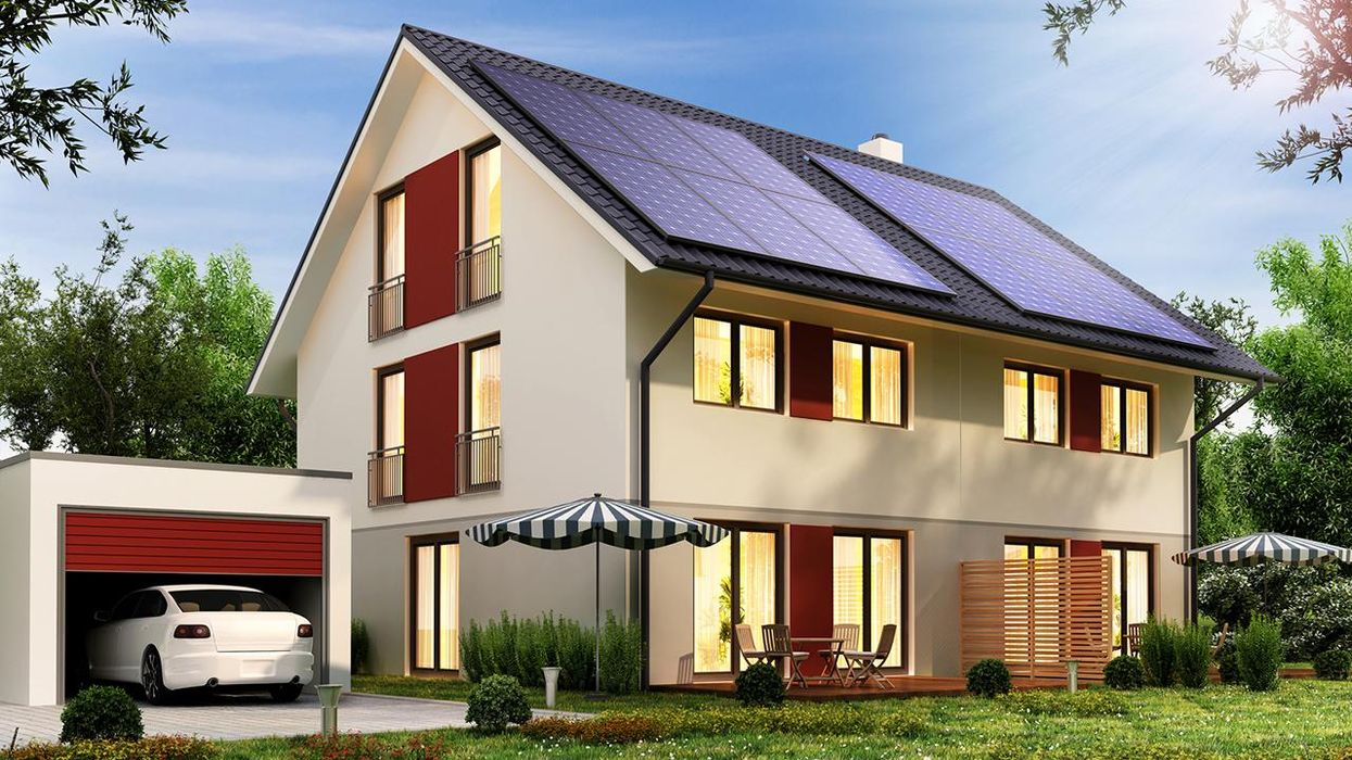 Solar panels on the roof of a modern house with a garage and a car