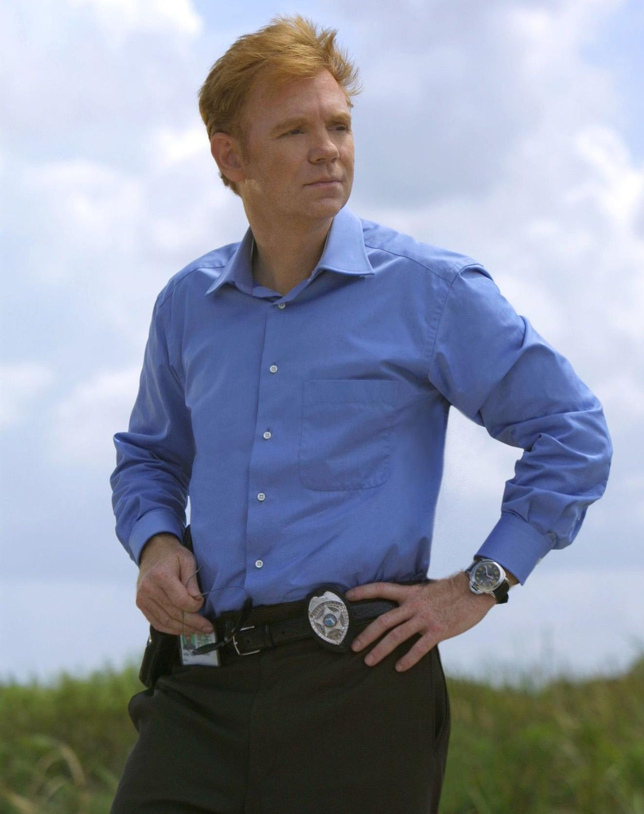 \u200bDavid Caruso as Horatio Caine standing in a field with his badge clipped to his belt