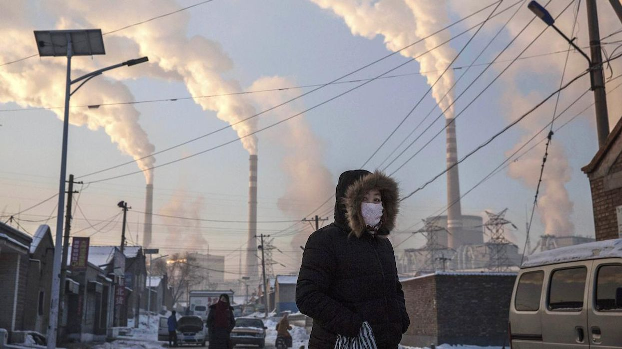 A woman walks near a coal-fired plant in China.