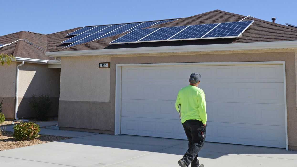 workman observing solar paneling on residential roof