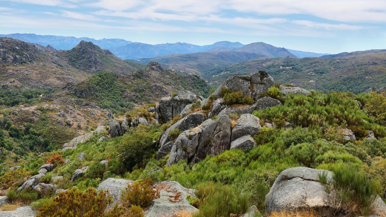 View of green mountains and stones from the ruins of Castro Laboreiro castle in Portugal