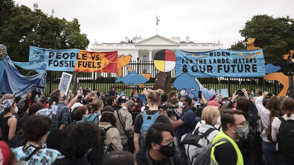 Demonstrators stand in front of the White House.