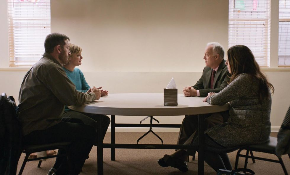 A photo of four people sitting around a table. They're two couples, with one couple sitting next to each other on one side, and the other couple is sitting far away on the other side of the table. A lone tissue box sits in between them.