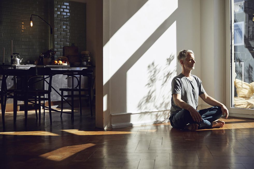 Man sitting on the floor at home meditating