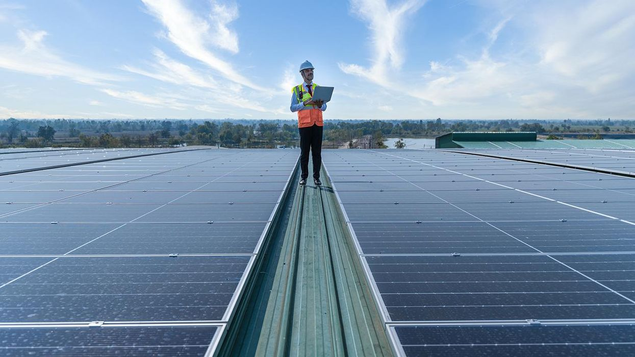 Engineers holding tablet standing at solar panels roof