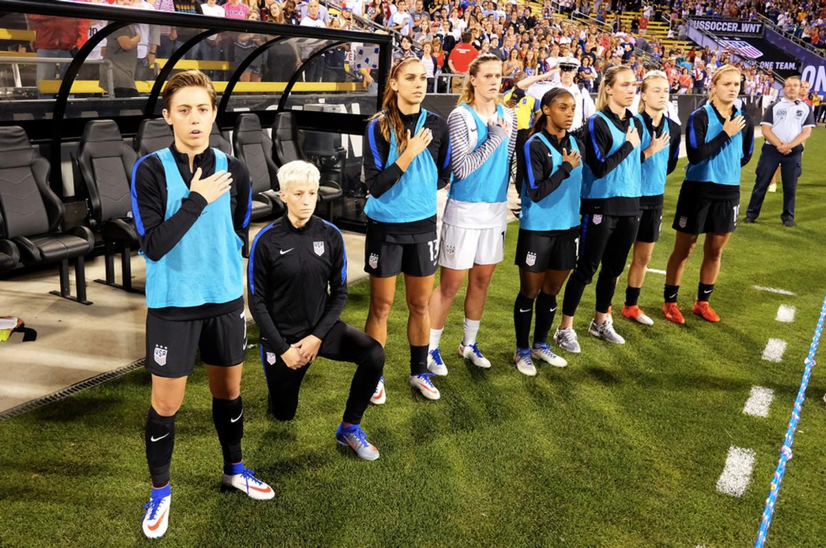 While Wearing A U.S. Uniform USWNT Midfielder Megan Rapinoe Kneels During The National Anthem